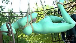 Latex Lucy Is Helpless Outdoors In Suspension Bondage. She Gets